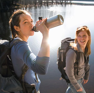 Backpacking women drinking water