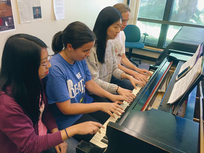 Four students playing piano