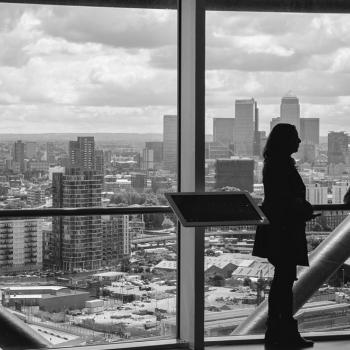 people in high-rise building looking at city view