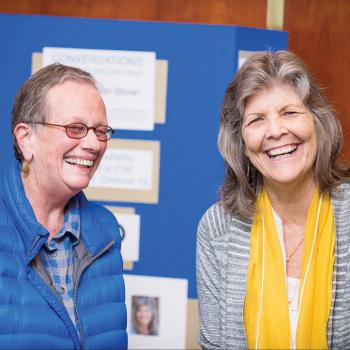 Two women laughing in conversation at open house event