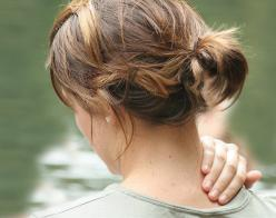 Woman massaging her neck and shoulder